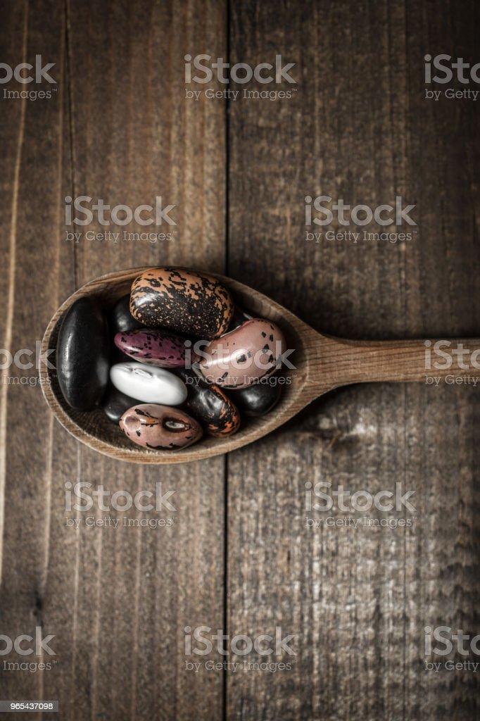 深色背景下的原始彩色豆類和木勺 - 免版稅乾燥食品圖庫照片