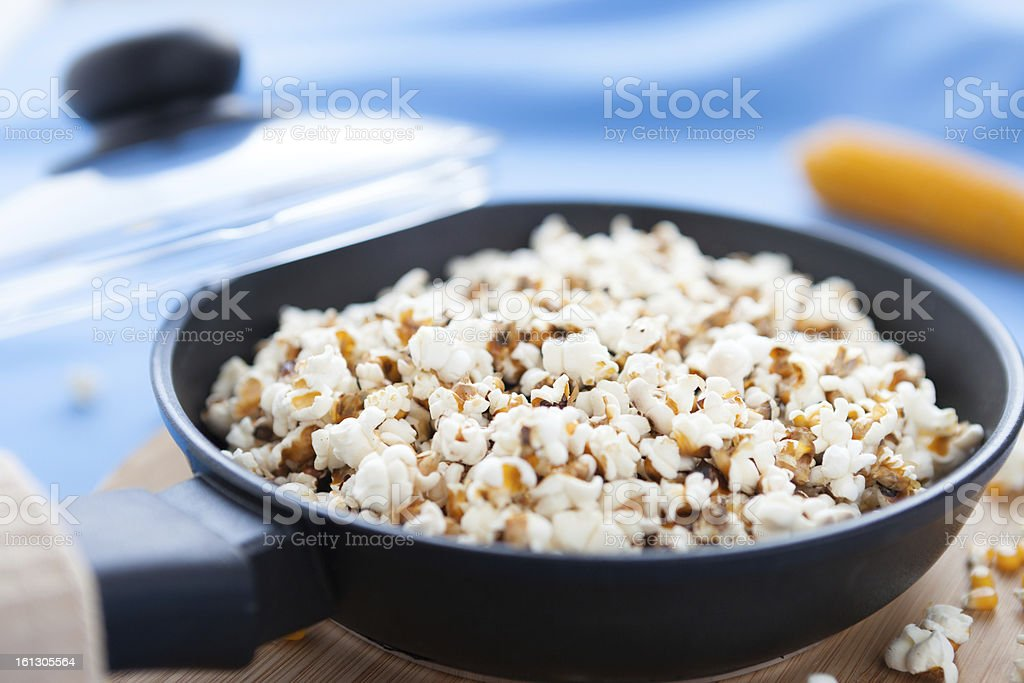 Raw corn and popcorn in a frying pan stock photo