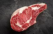 istock raw cowboy steak on stone background, prime rib eye on bone, top view 1230892196