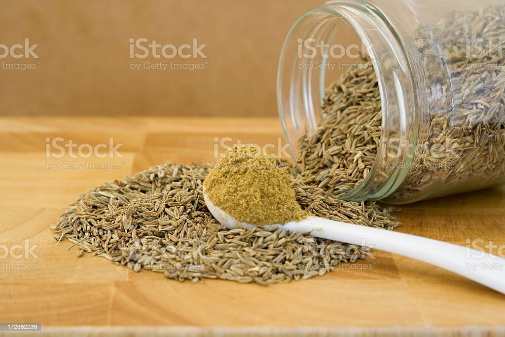 Raw cumin pouring out of a glass container onto wooden board stock photo