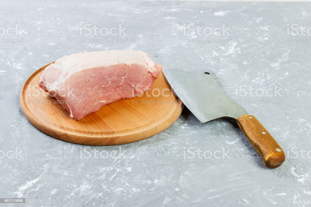 Raw cut of pork shoulder on board with knife or Kitchen ax. cleaver with fresh raw meat on black wooden background stock photo