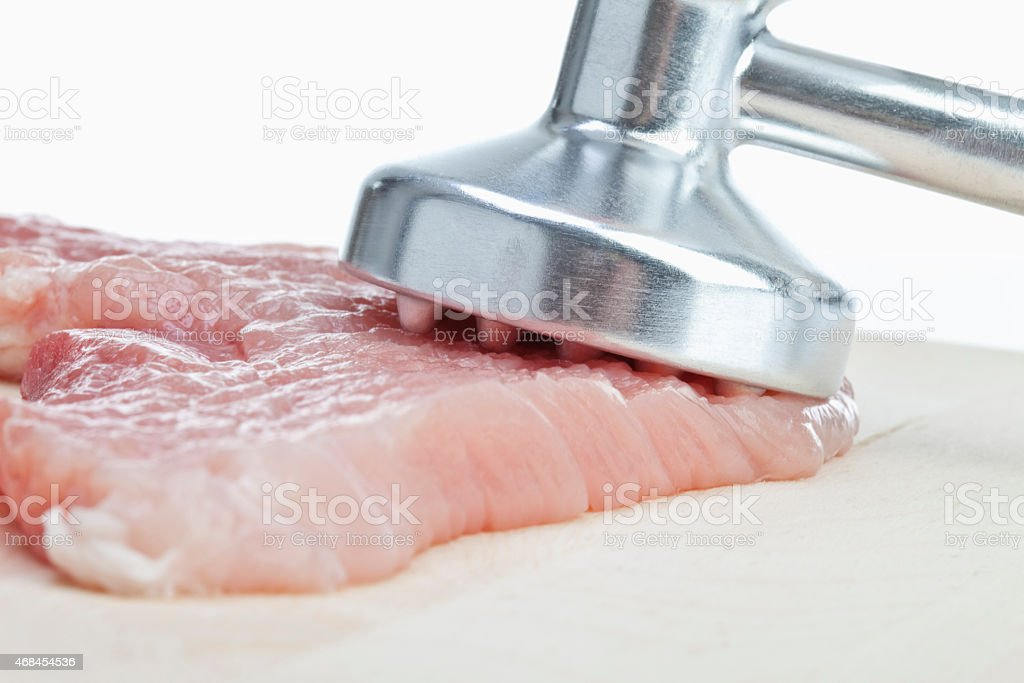 Raw cutlet and meat tenderizer, close-up stock photo