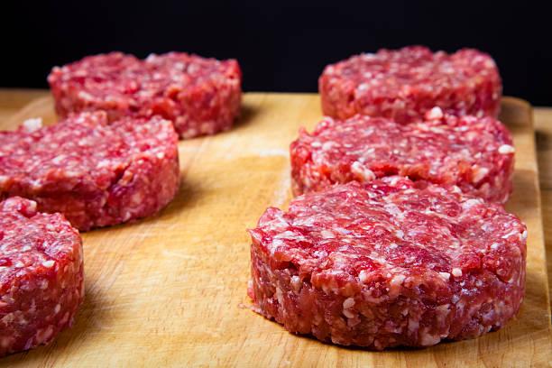 raw schnitzel von hackfleisch auf einer hölzernen schneidebrett  - frikadelle stock-fotos und bilder