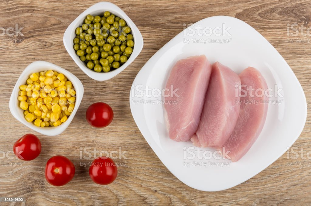 Raw cutlets from turkey, tomato, sweet corn and green peas stock photo