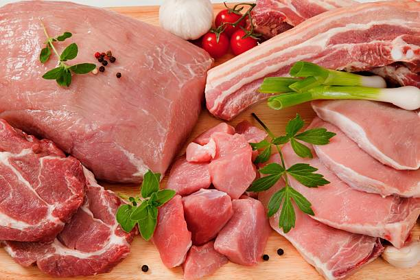 Raw cuts of pork meat on a wooden chopping board Various cuts of pork meat on a chopping board pork stock pictures, royalty-free photos & images