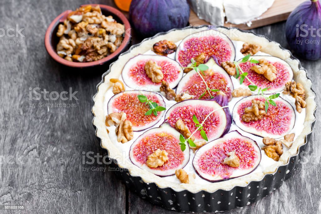 Raw  delicious tart with fresh figs and goat cheese on rustic wooden table. Ready for baking. stock photo