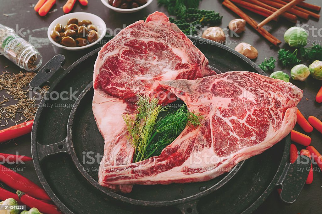 Raw double tomahawk beef steak with ingredients for grilling stock photo