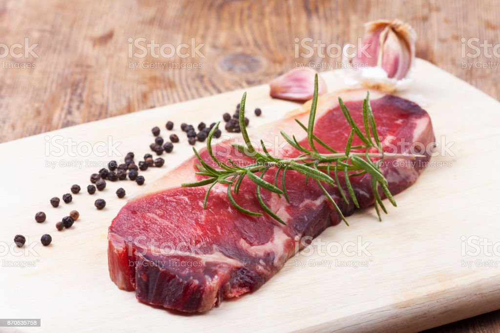 raw dry aged steak on wood stock photo