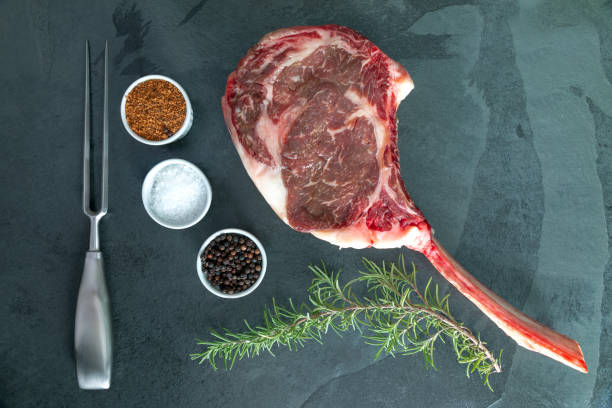 Raw, dry-aged wagyu tomahawk steak, salt,pepper, bbq rub and rosemary on a  black stone table. Top view stock photo