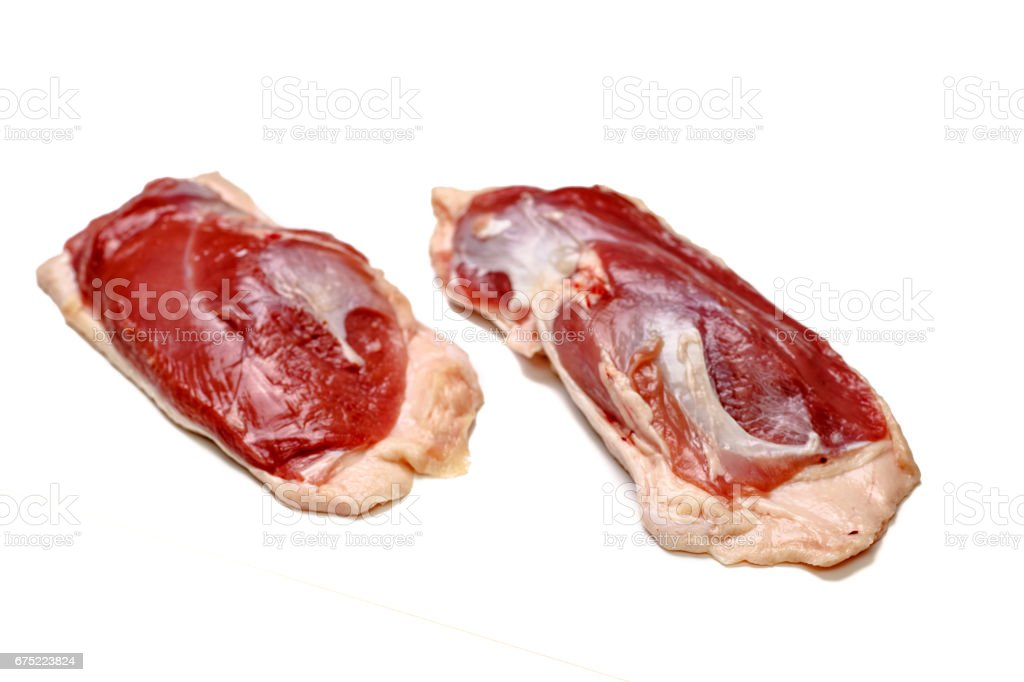 Raw duck breast lying on a white background, not isolated, with a shadow. royalty-free stock photo