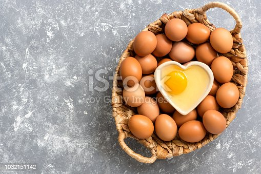 istock A raw egg in a bowl in the shape of a heart, a basket with brown eggs on a gray background. Top view, copy space, flat lay 1032151142