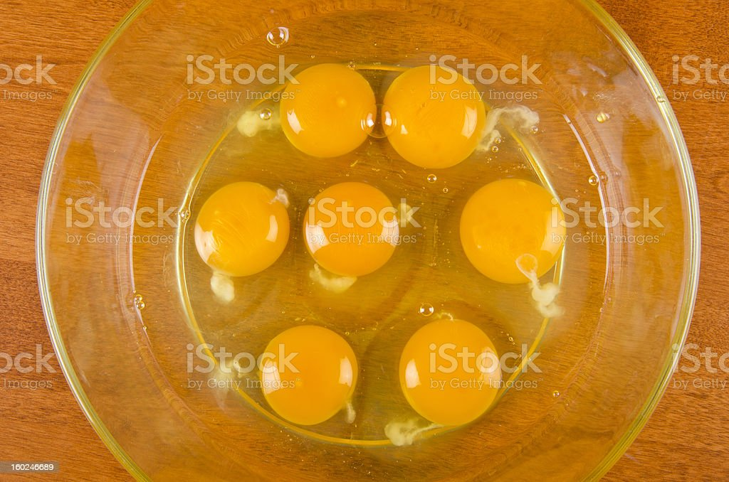raw egg whites and yolks in a Pyrex glass mixing bowl stock photo