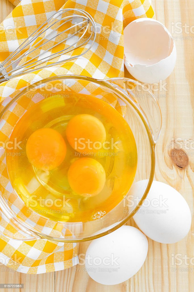 Raw eggs and whisk stock photo