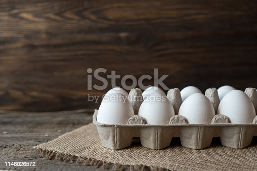 Raw white eggs in egg box on wooden background.