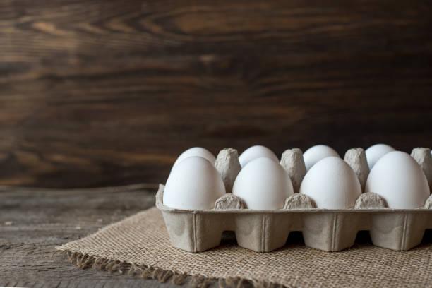 rauwe eieren in eierdoos op houten achtergrond. - chicken bird in box stockfoto's en -beelden