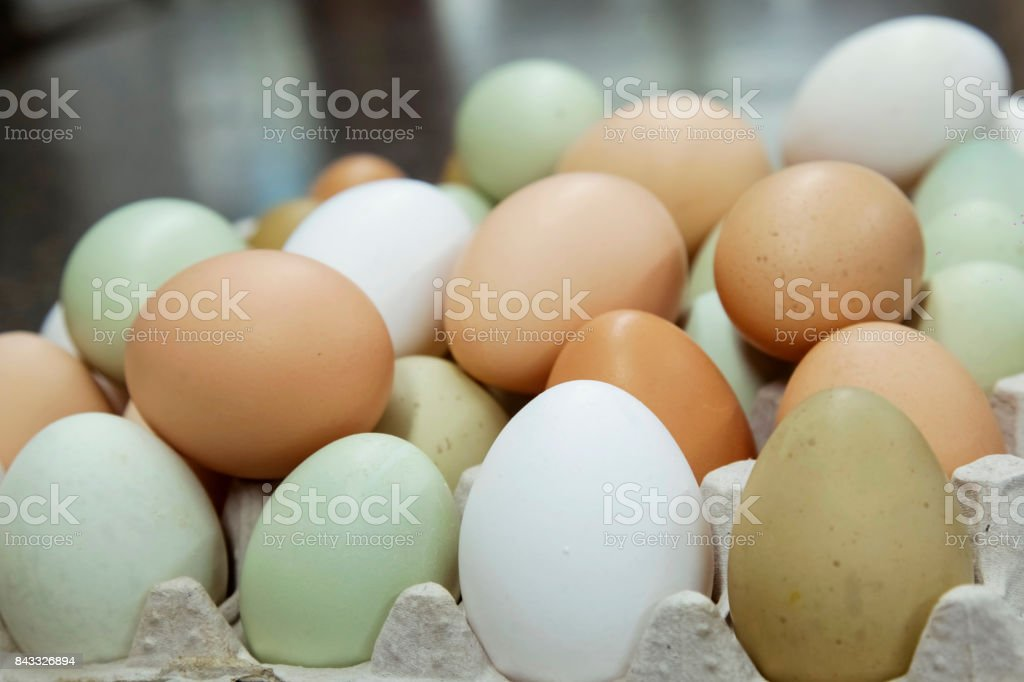 Raw eggs in package on color background stock photo