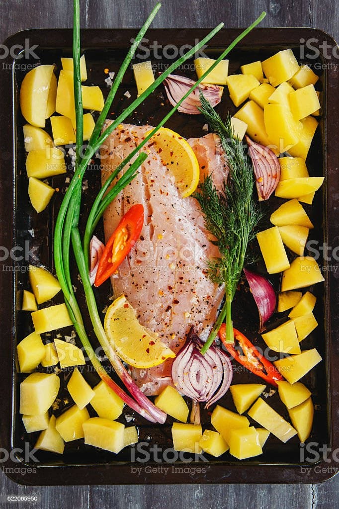 Raw fish fillet with potatoes ready for the oven stock photo