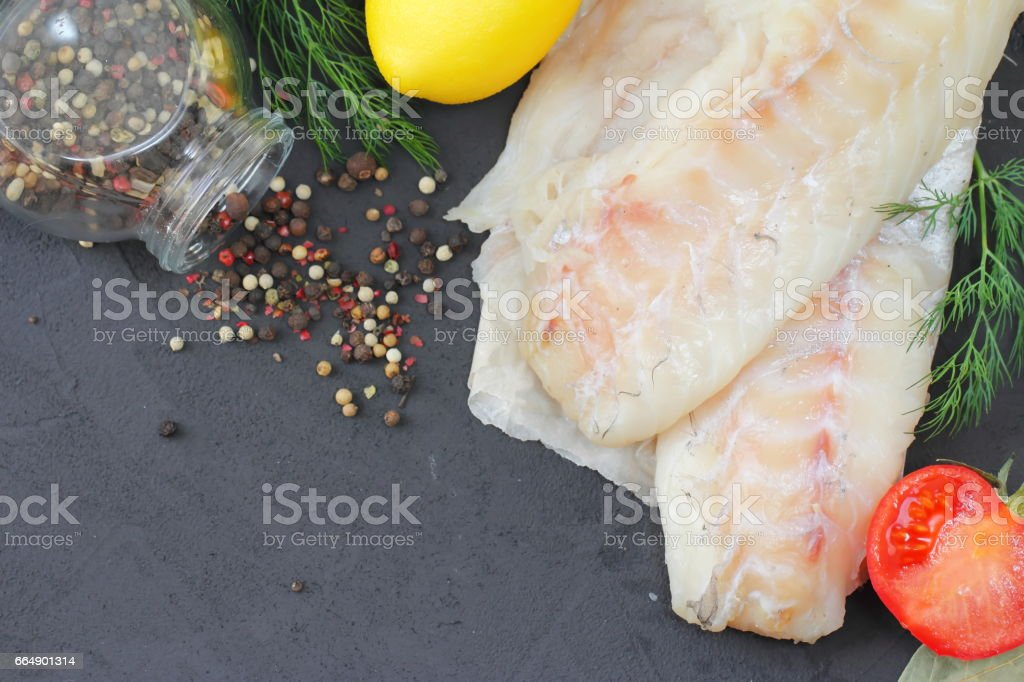 Raw fish fillet with spices and lemon stock photo