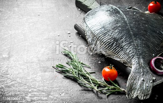 Raw fish flounder with tomatoes, onion slices and rosemary. On dark rustic background