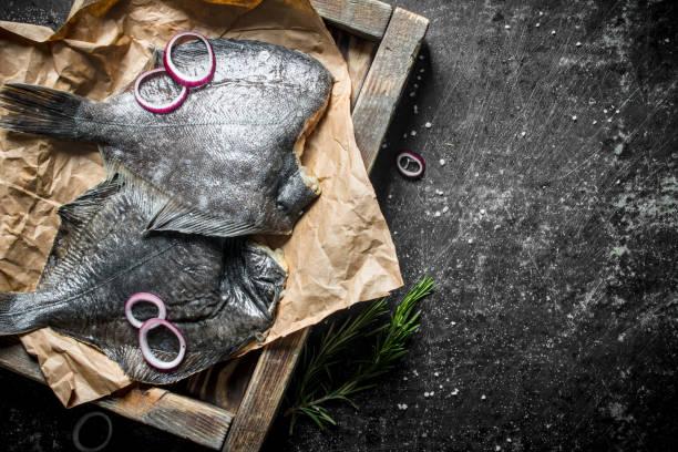 pescado crudo en bandeja con ajo, cebolla picada y romero. - rodaballo fotografías e imágenes de stock