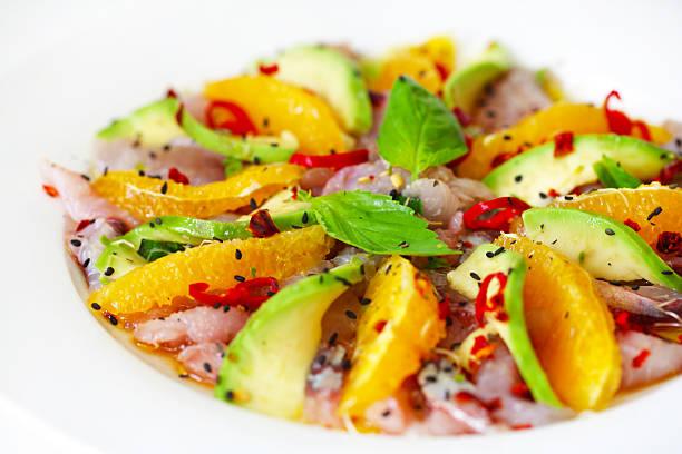 roher fisch-salat-carpaccio mit avocado und orangenscheiben - carpaccio salat stock-fotos und bilder