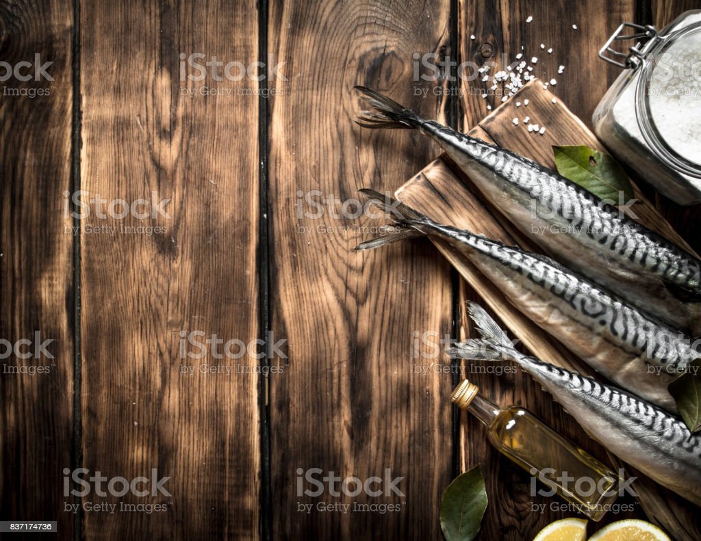 Raw fish with spices on a cutting Board. stock photo