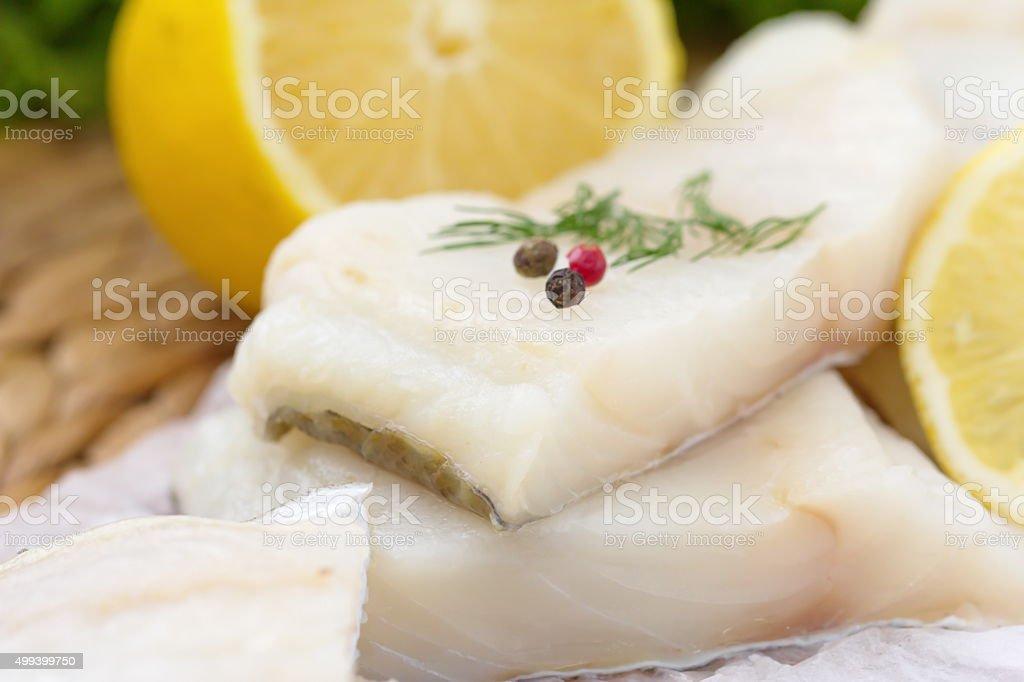 Raw fish with vegetables, lemon and seasonings stock photo