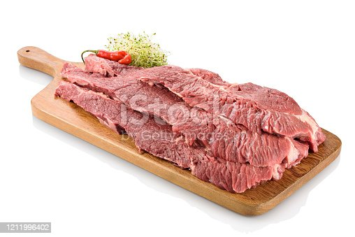 Raw flank steak, a cut of beef taken from the abdominal muscles or lower chest of the steer, ready to be cooked. On a cutting board with peppers aside, isolated on white background