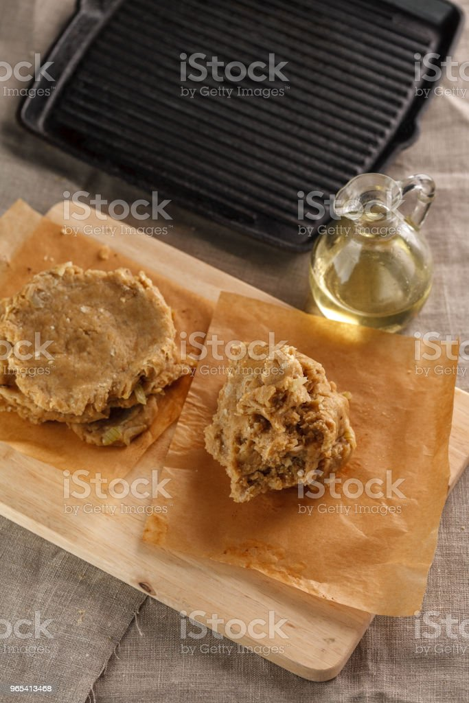 raw flat bread and a carafe of oil on the cutting Board on the background of the grill zbiór zdjęć royalty-free