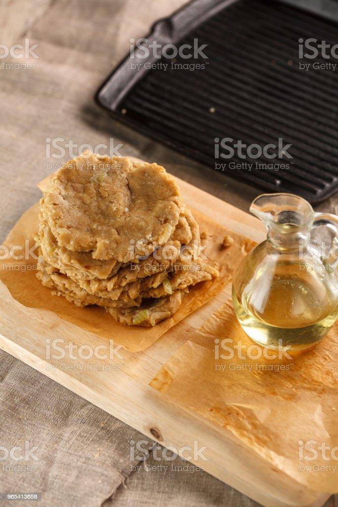 rohe Fladenbrot und eine Karaffe mit Öl auf des Messers Schneide Brett auf dem Hintergrund des Grills - Lizenzfrei Backen Stock-Foto