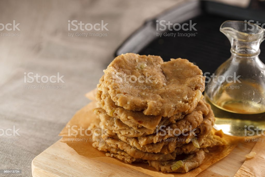 raw flat bread and a carafe of oil on the cutting Board on the background of the grill royalty-free stock photo