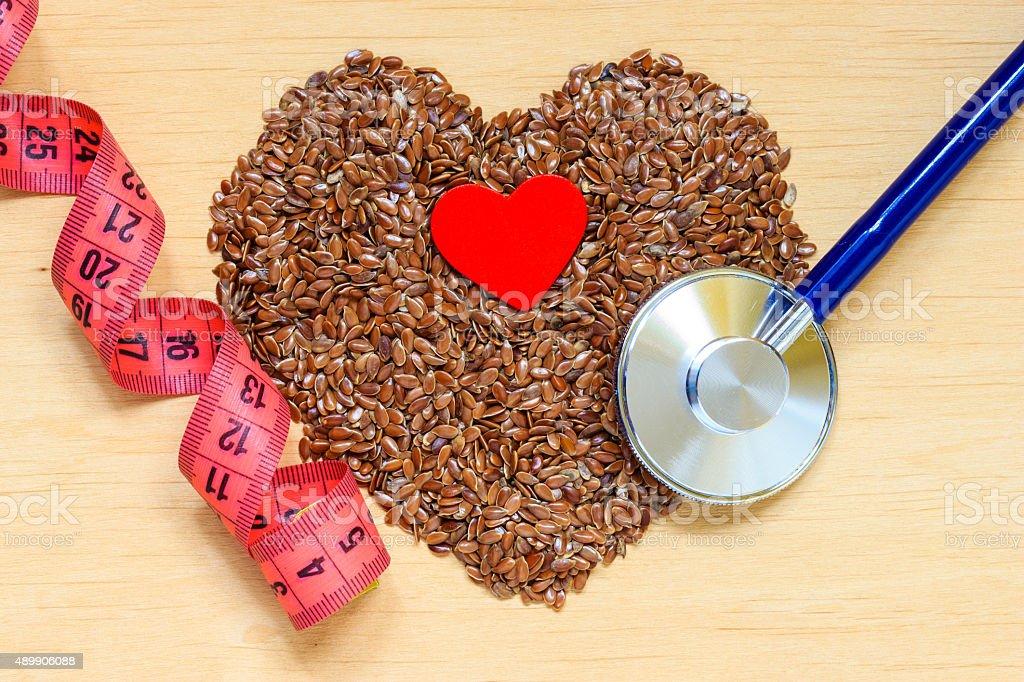 Materias primas lino semillas en forma de corazón y un estetoscopio - foto de stock