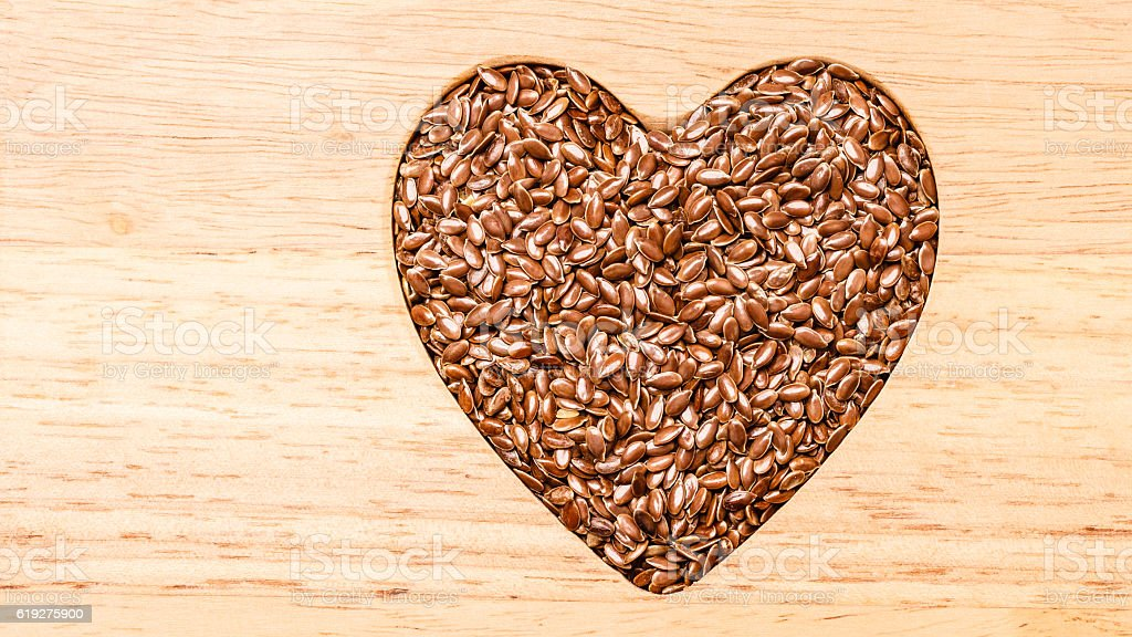 Raw flax seeds linseed heart shaped stock photo