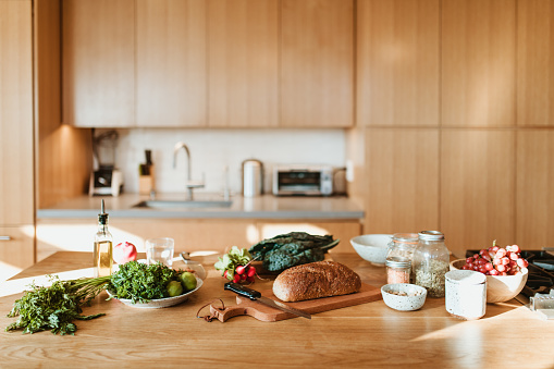 Raw food and ingredients on kitchen island at home