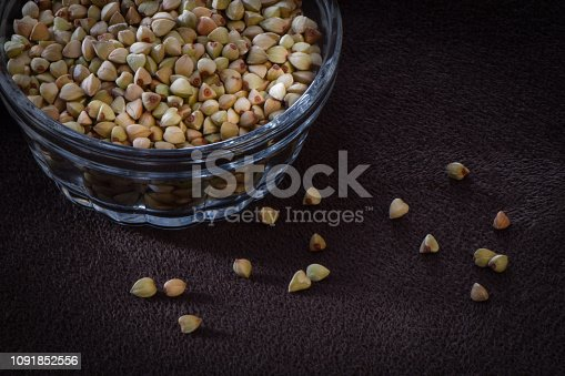 Gluten Free organic buckwheat cereal seed in a glass bowl, with several scattered below, on a dark surface with faint vignette.
