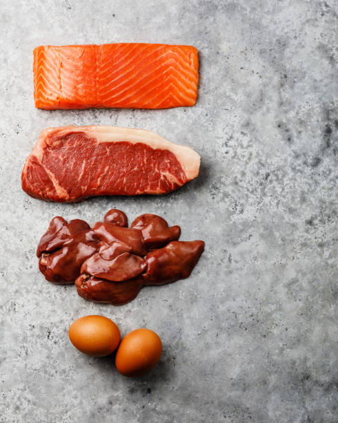 Raw food selection for Ketogenic diet Egg, Chicken Liver, Beef meat Steak and Salmon fish Steak on gray concrete background copy space stock photo