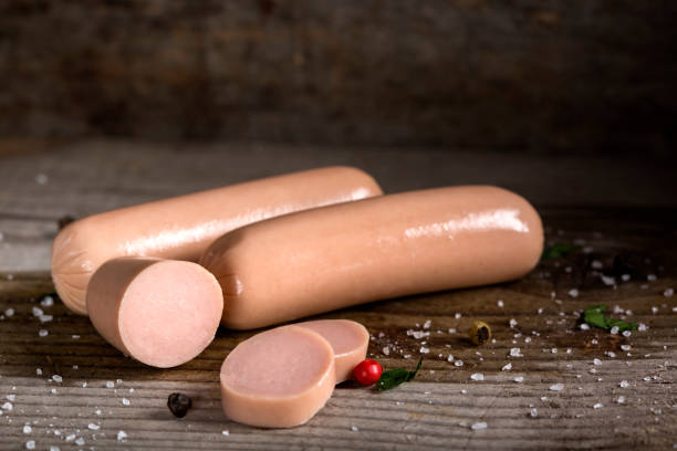 Raw frankfurter sausages with spices stock photo