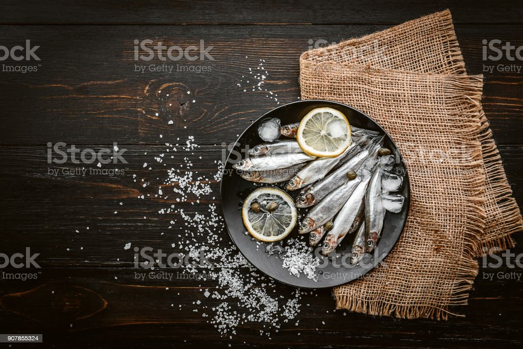 raw fresh fish on a plate with salt and lemon in a rustic style on a wooden surface stock photo
