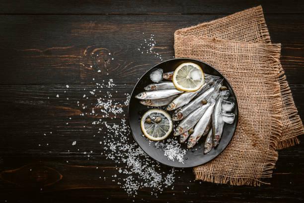 materia prima pescado fresco en un plato con sal y limón en un estilo rústico en una superficie de madera - anchoa fotografías e imágenes de stock