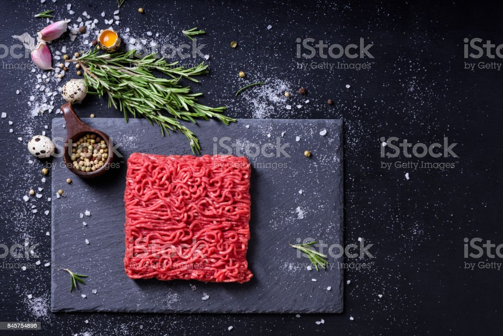 Raw fresh marbled mince meat and seasonings on dark background. stock photo