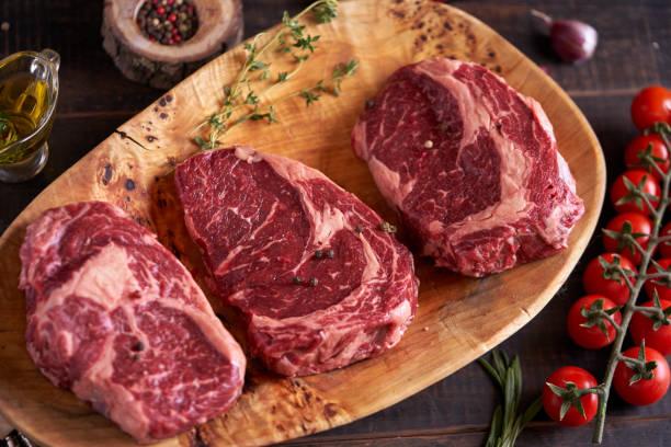 rauw vers vlees rib eye steak op een cutting houten bord met rozemarijn, rode tomaten, peperkorrels, olijfolie, uien en knoflook. bbq-koken. vleesingrediënten. restaurant menu. uitzicht vanaf boven - ribeye biefstuk stockfoto's en -beelden