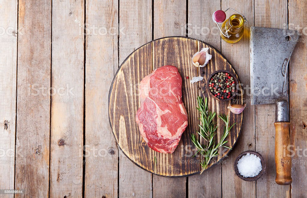 Raw fresh meat Steak with salt and pepper, rosemary, tomatoes stock photo
