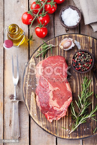 808351094 istock photo Raw fresh meat Steak with salt and pepper, rosemary, tomatoes 535459626