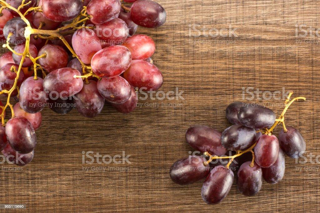 Raw fresh red globe grape on brown wood stock photo