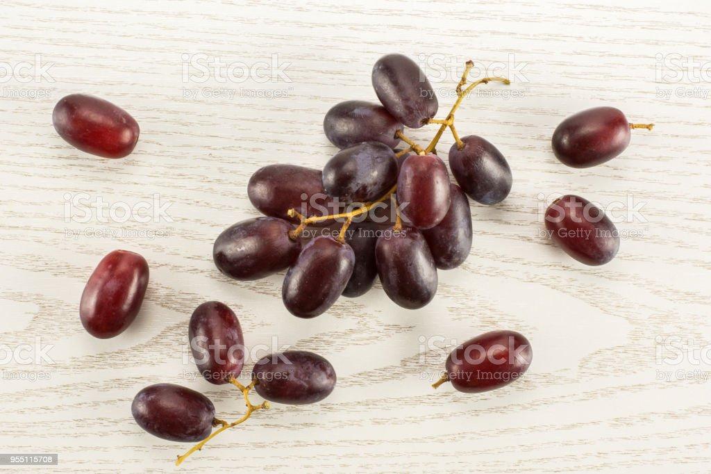 Raw fresh red globe grape on grey wood stock photo