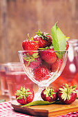 raw ripe fresh srrawberry in glass containeer with compote in studio