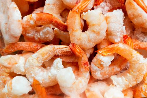 Raw frozen and peeled shrimp background. Pile of frozen shrimps  .Close-up of frozen shrimps. A lot of royal shrimp macro shot