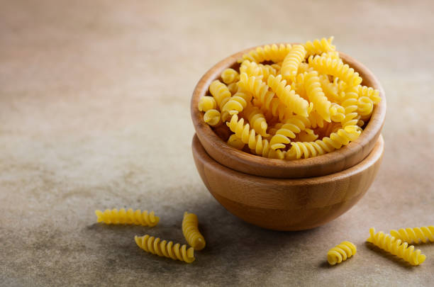 Raw fusilli pasta in a wooden bowl. Raw fusilli pasta in a wooden bowl, selective focus, copy space. fusilli stock pictures, royalty-free photos & images