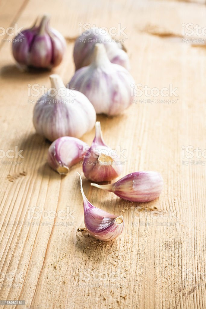 raw garlic on a wooden plank royalty-free stock photo