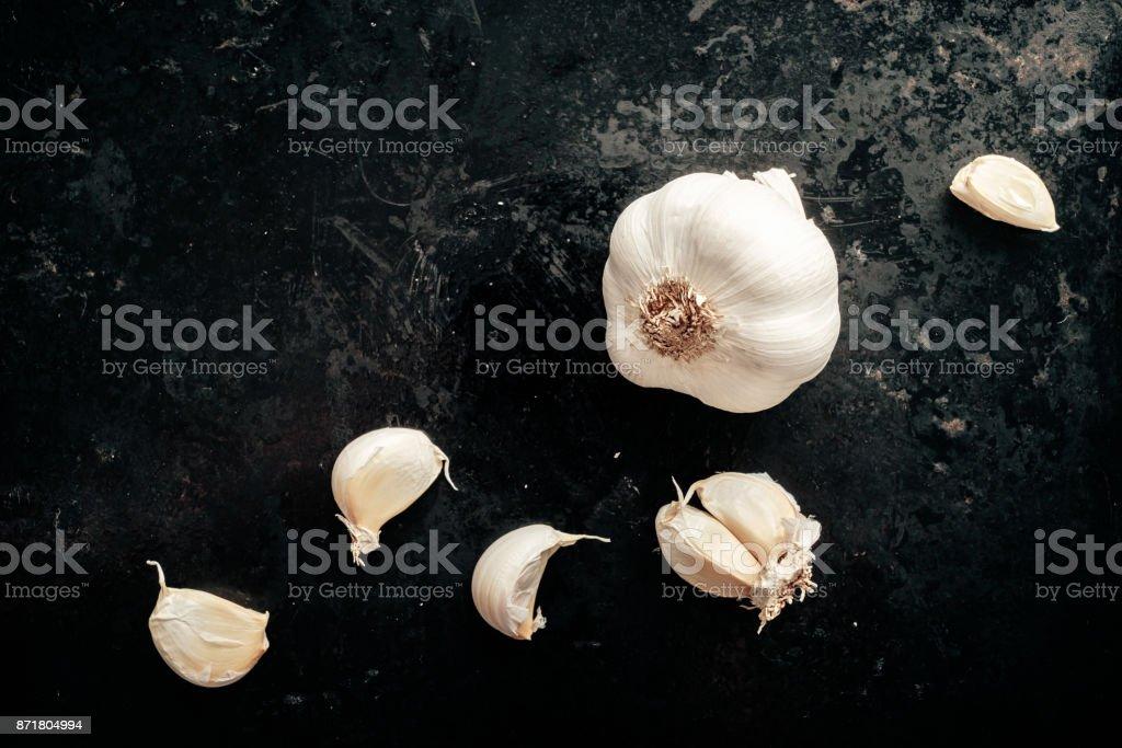 Raw garlic on black background. stock photo